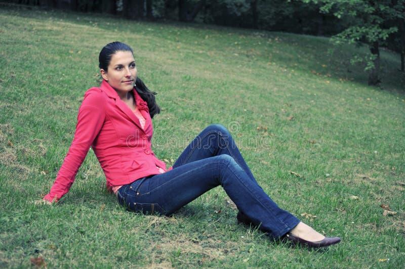 草坪坐的妇女 库存图片