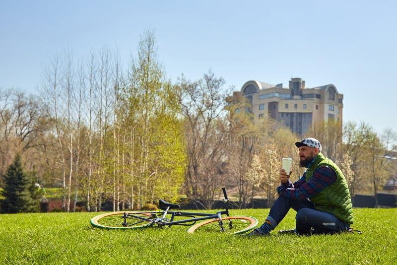 草坪的年轻人有自行车的 他在他的手上拿着一杯咖啡 免版税库存照片