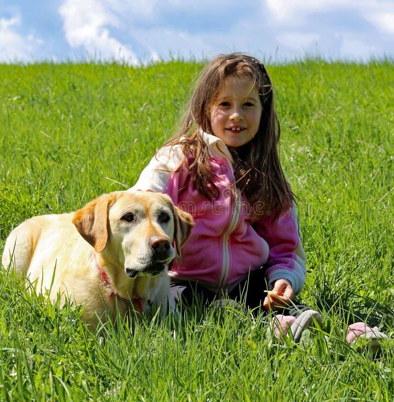 草坪的微笑的小女孩有看家狗的 库存图片