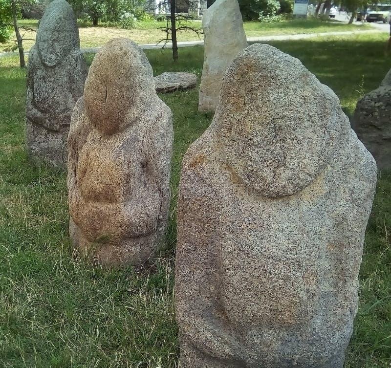 草坪的Scythian石妇女在城市博物馆附近 古老灰色石雕塑 免版税图库摄影