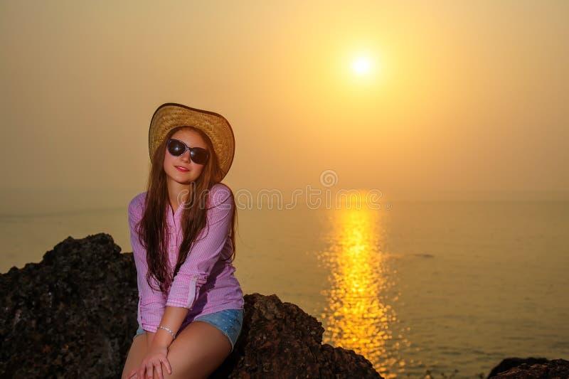 草帽、太阳镜和桃红色衬衣的年轻俏丽的微笑的妇女坐岩石反对海和天空 在水的太阳道路 库存照片