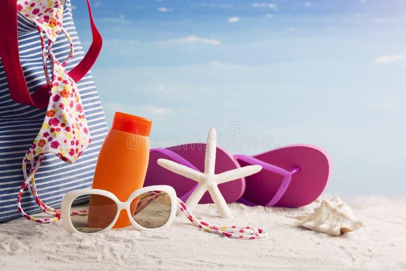 草帽、袋子、太阳镜和触发器在一个热带海滩 免版税库存图片