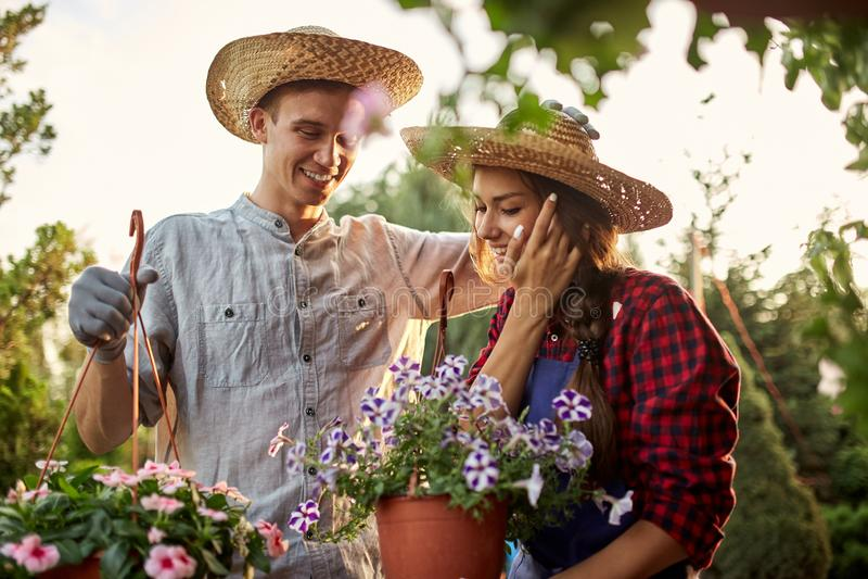 草帽举行罐的愉快的人和女孩花匠有在庭院道路的喇叭花的在一好日子 图库摄影
