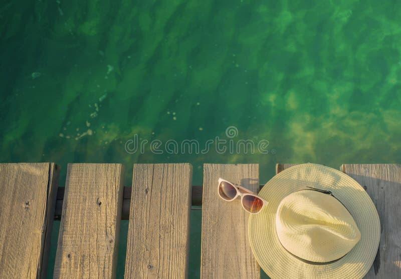 草帽和太阳镜顶视图在木桥在鲜绿色海水 暑假旅行背景 夏天vibe 库存照片