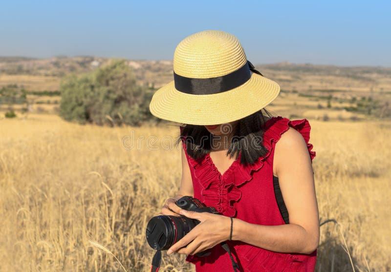 草帽和红色短小的妇女拿着一台照相机 准备的妇女拍在一个黄色领域的照片 免版税图库摄影