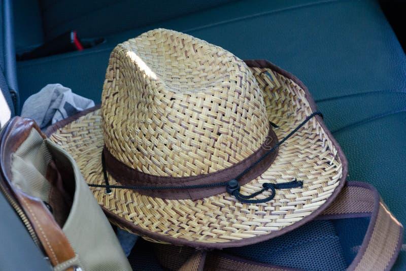 草帽和袋子在汽车位子  免版税库存图片