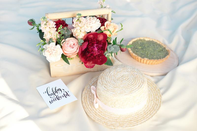 草帽在一条白色野餐毯子放置绿色草坪明亮的夏日 免版税图库摄影