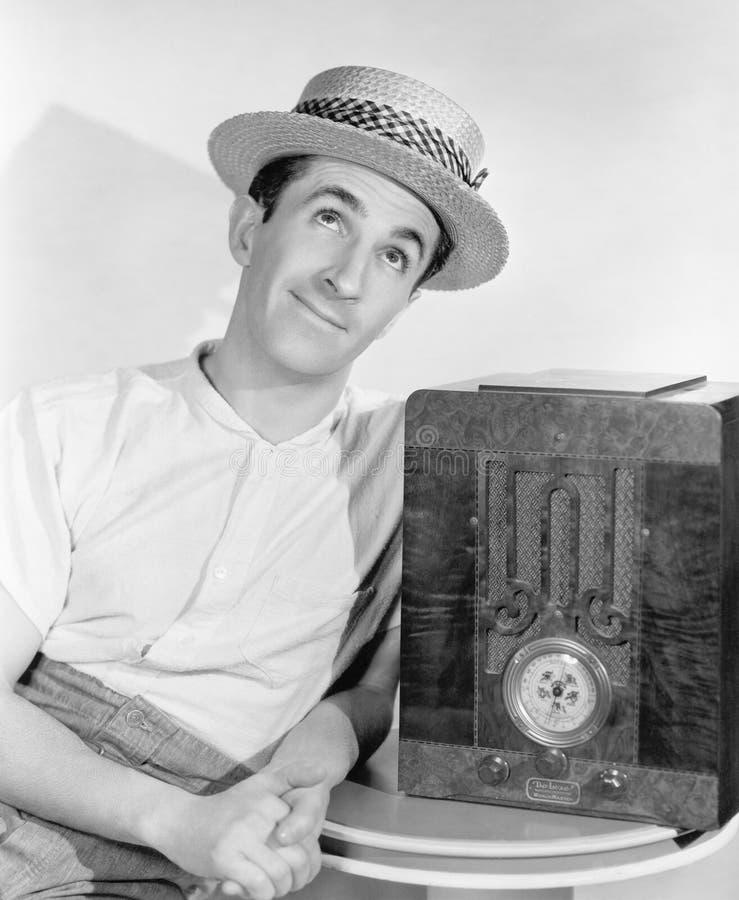草帽的人听到收音机的(所有人被描述不更长生存,并且庄园不存在 供应商保单tha 库存照片