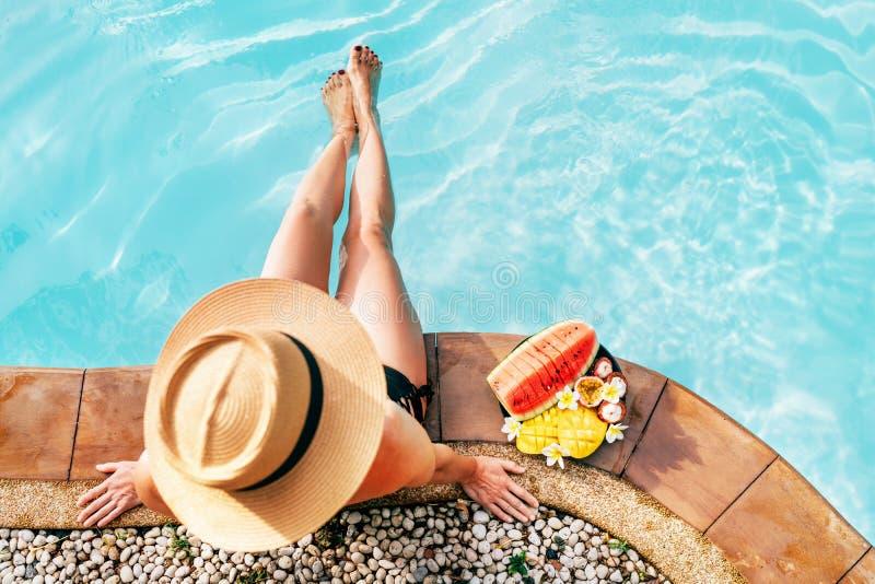草帽的妇女坐与热带水果照相机顶视图板材的游泳场边  图库摄影