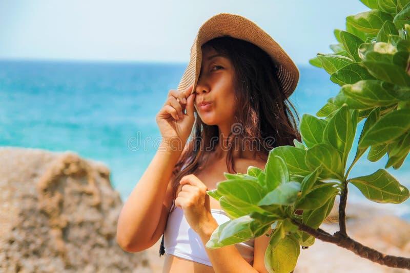 草帽的愉快的微笑的亚裔妇女在海海滩 免版税库存照片