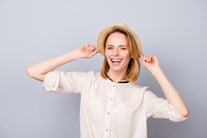 草帽的愉快的微笑的妇女有乐趣和身分反对 免版税库存图片