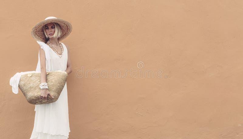 草帽的金发碧眼的女人和白色穿戴与时髦的辅助部件袋子 免版税库存照片