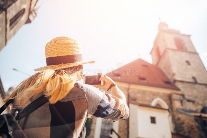 草帽的,格子衬衫白肤金发的女孩拍在欧洲石头大厦中世纪建筑学电话的照片  库存照片