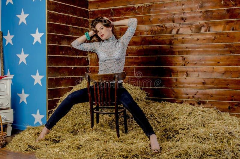 草料棚的年轻美丽的亭亭玉立的女孩 免版税库存照片