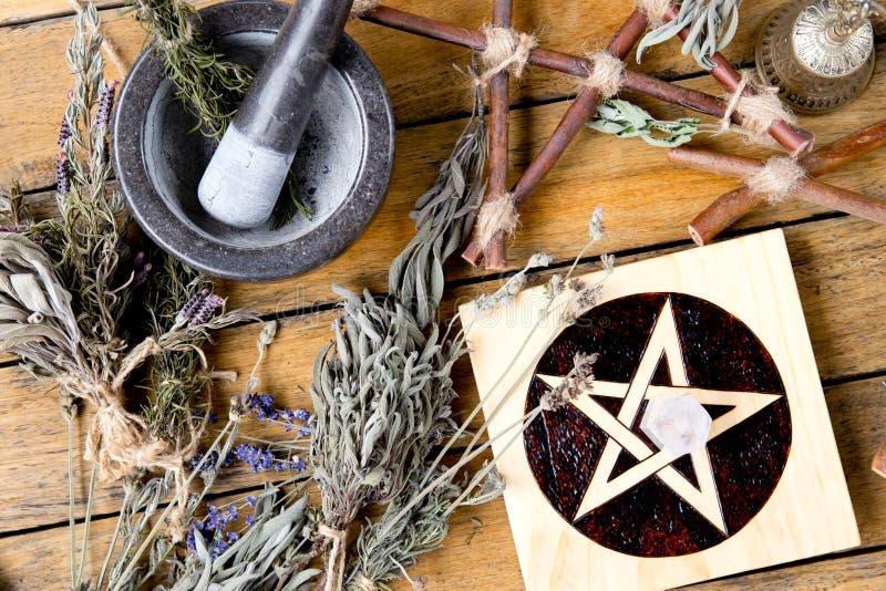 草本与灰浆的巫婆工作和杵、五芒星形法坛瓦片有干草本捆绑的和黄铜响铃在木背景 免版税图库摄影