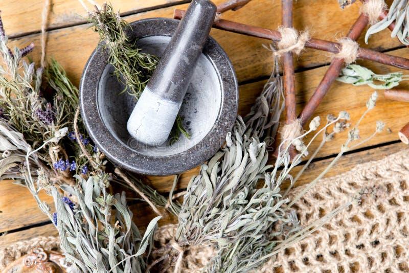 草本与灰浆的巫婆工作和杵、分支五角星形和干草本捆绑 免版税库存图片