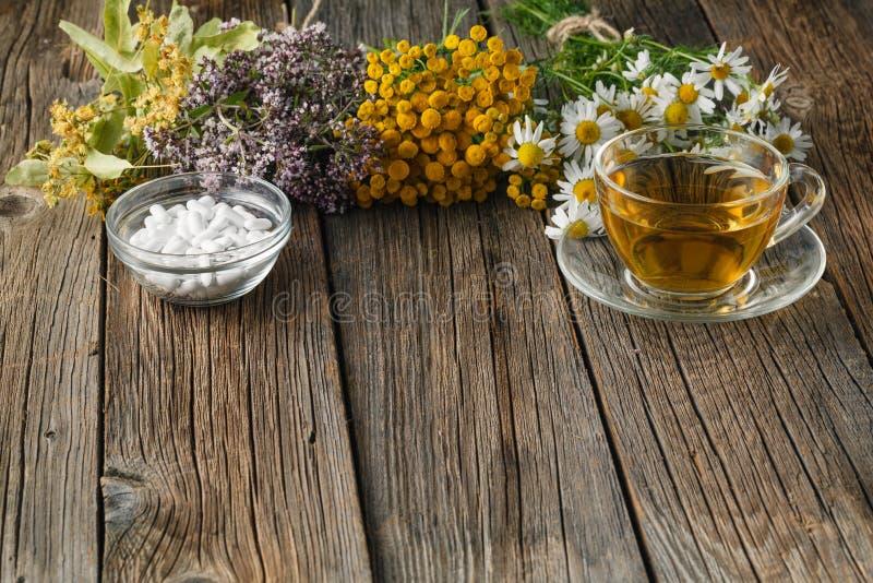 医治草本和碗在木桌上的药片 库存照片