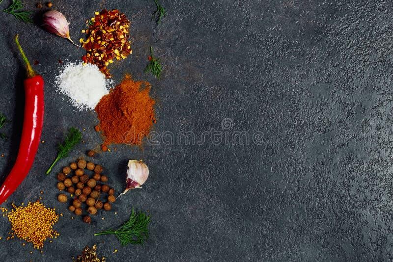 草本和香料在黑石背景 r 库存图片