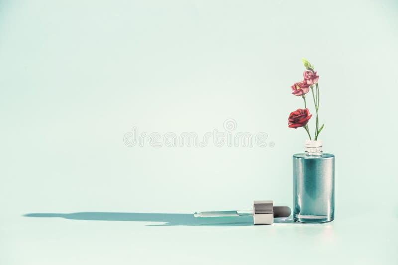 草本护肤化妆用品和秀丽概念 有吸管的面部血清或油瓶或吸移管和花 库存照片