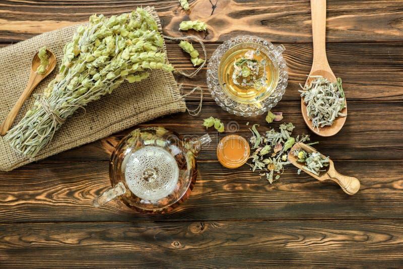草本混合物概念-茶叶,在木背景,顶视图的茶壶 库存图片