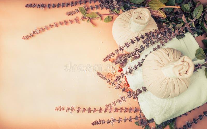 草本温泉、健康或按摩设置用新鲜的草本和花,压缩球和毛巾在自然米黄背景,名列前茅vi 免版税库存照片