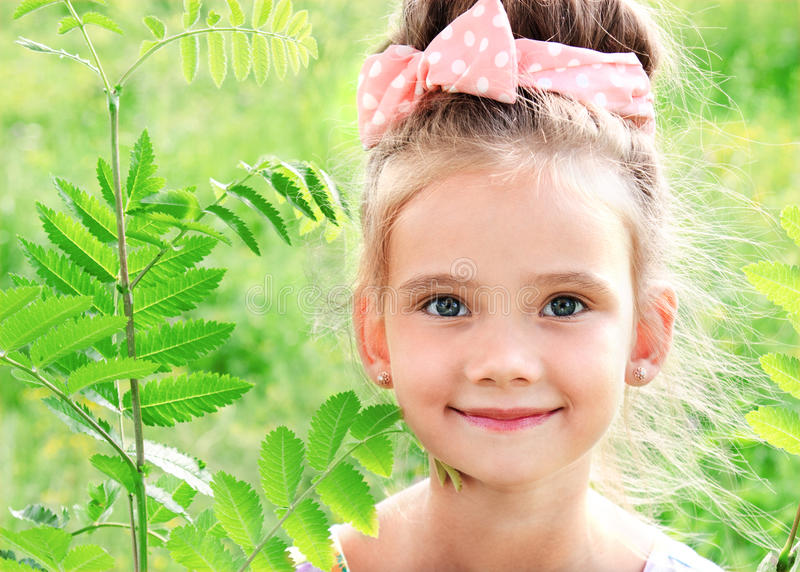 草甸的可爱的微笑的小女孩在夏日 免版税库存照片