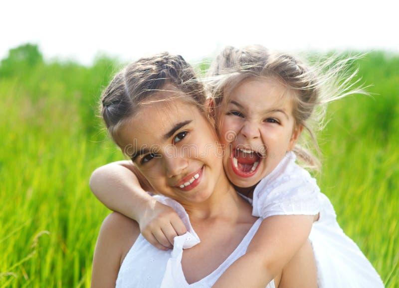 草甸的微笑的愉快的小女孩 免版税库存图片