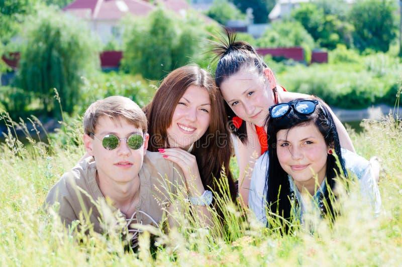 绿草的四个愉快的微笑的青少年的朋友户外 免版税库存图片