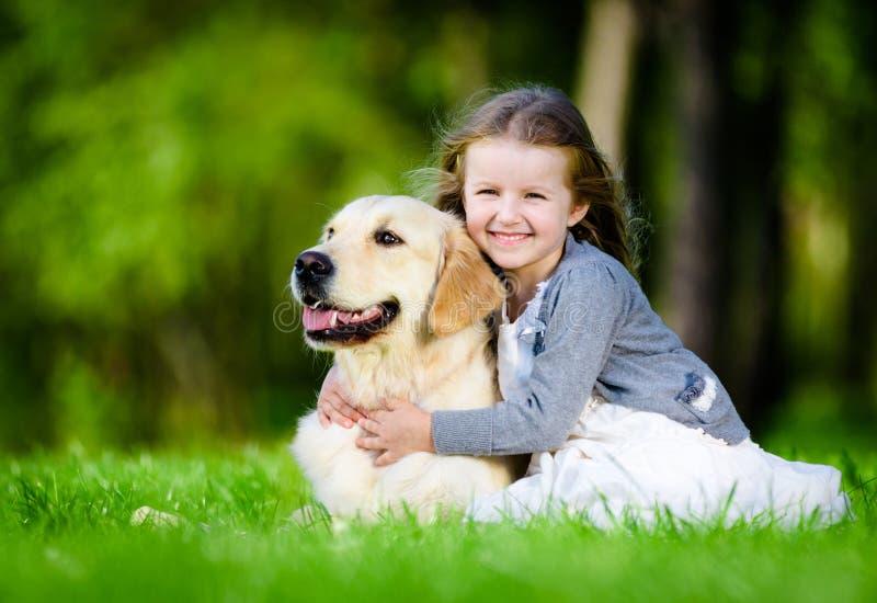 草的女孩与拉布拉多在公园 库存照片