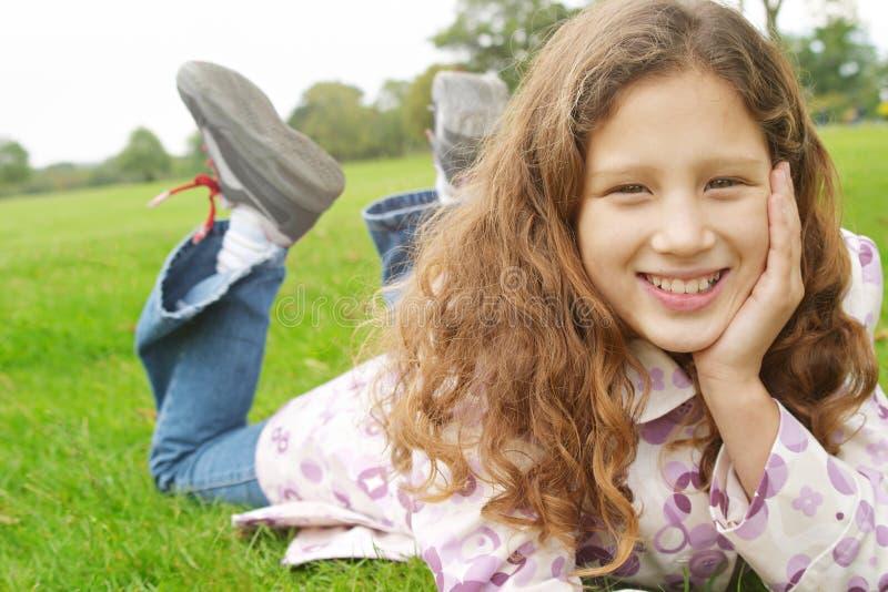 草的女孩在公园。 免版税库存图片