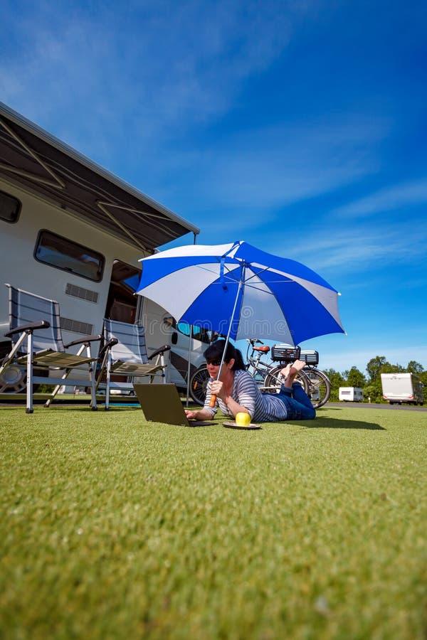草的妇女,看膝上型计算机在伞下在Th附近 免版税图库摄影
