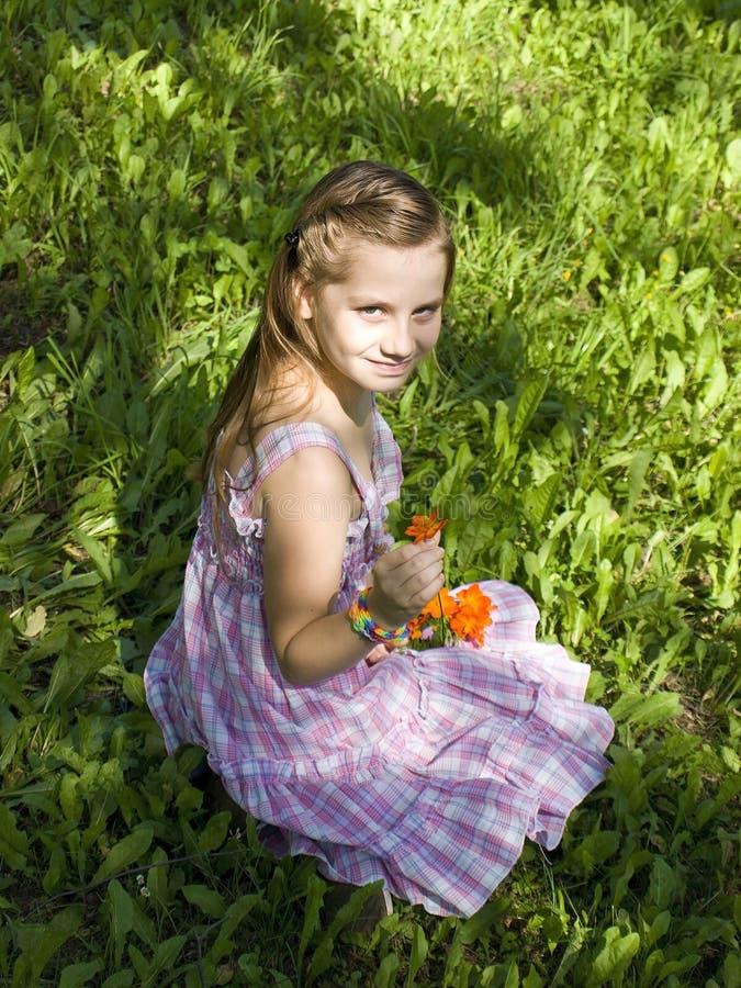 草的微笑的女孩与花 免版税库存图片