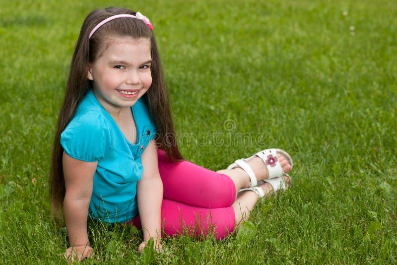 草的愉快的小女孩 库存照片