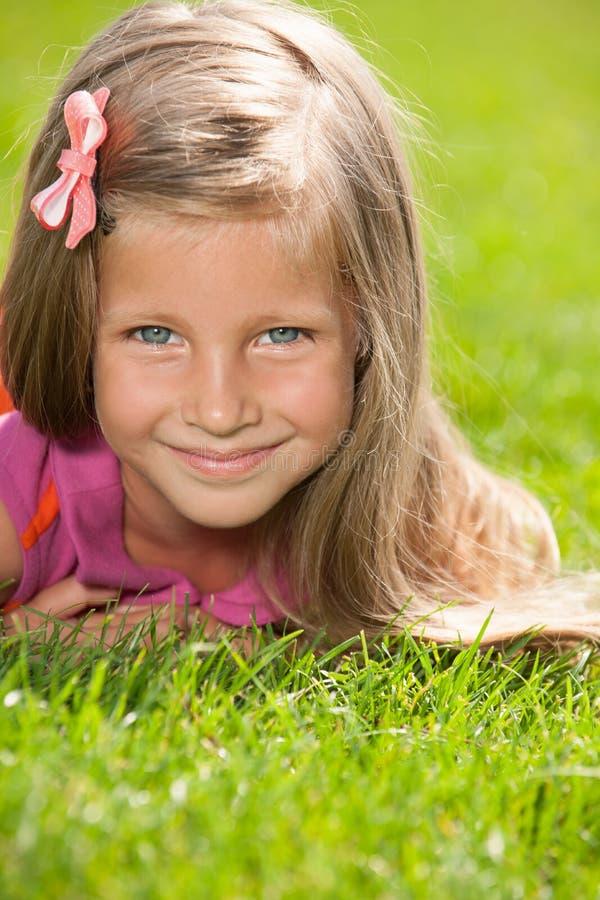 草的愉快的小女孩 免版税库存照片