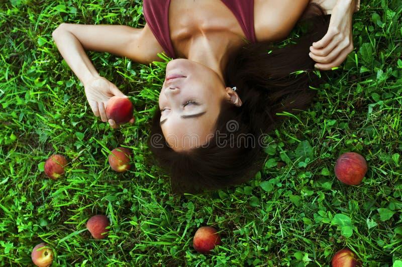草的美丽的妇女用桃子 库存图片
