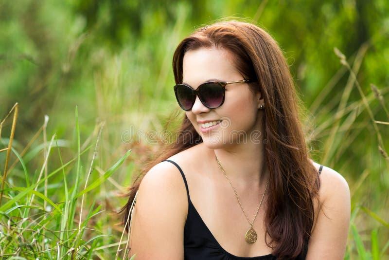 草的美丽的微笑的妇女 库存图片