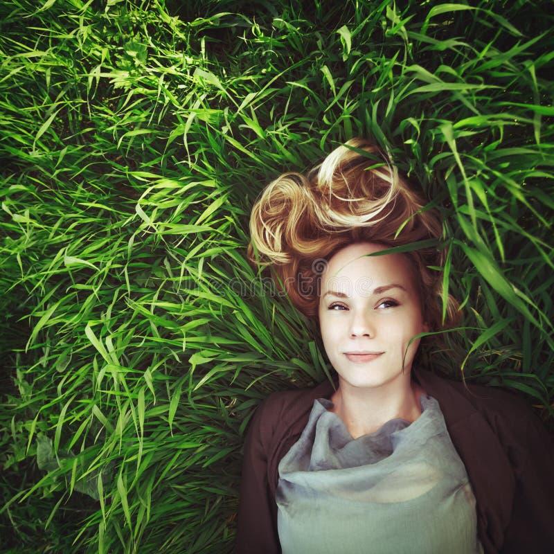 草的美丽的年轻冥想的妇女。Instagram作用。 免版税库存照片