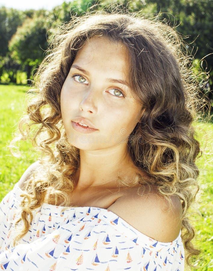 绿草的年轻逗人喜爱的夏天女孩在松弛微笑的关闭之外  免版税库存图片