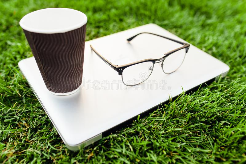 草绿色膝上型计算机 咖啡和玻璃 办公室和workin 免版税图库摄影