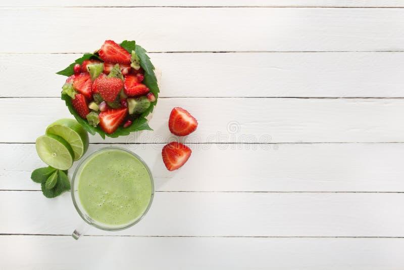 草莓、猕猴桃和石榴在一个柳条筐和新鲜的绿色圆滑的人水果沙拉与石灰和薄菏在玻璃 免版税库存照片