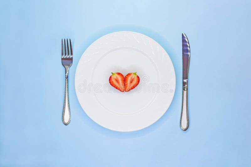 草莓一半的心脏在白色板材的 低卡路里食物概念 Vegeterian未加工的食物 r 库存照片