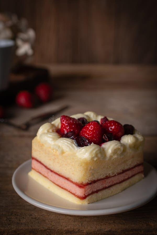 草莓冠上草莓的夹心蛋糕投入在木桌背景的白色板材 免版税库存图片