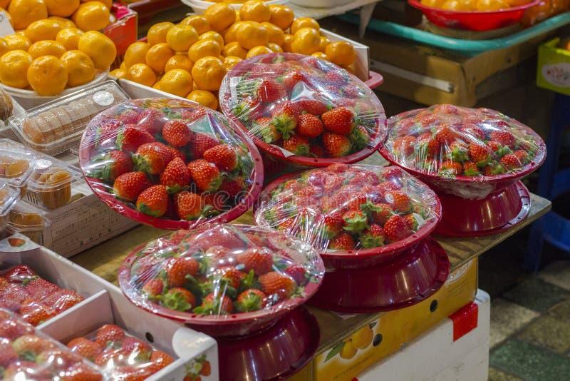 草莓和桔子在夜市场上 库存图片