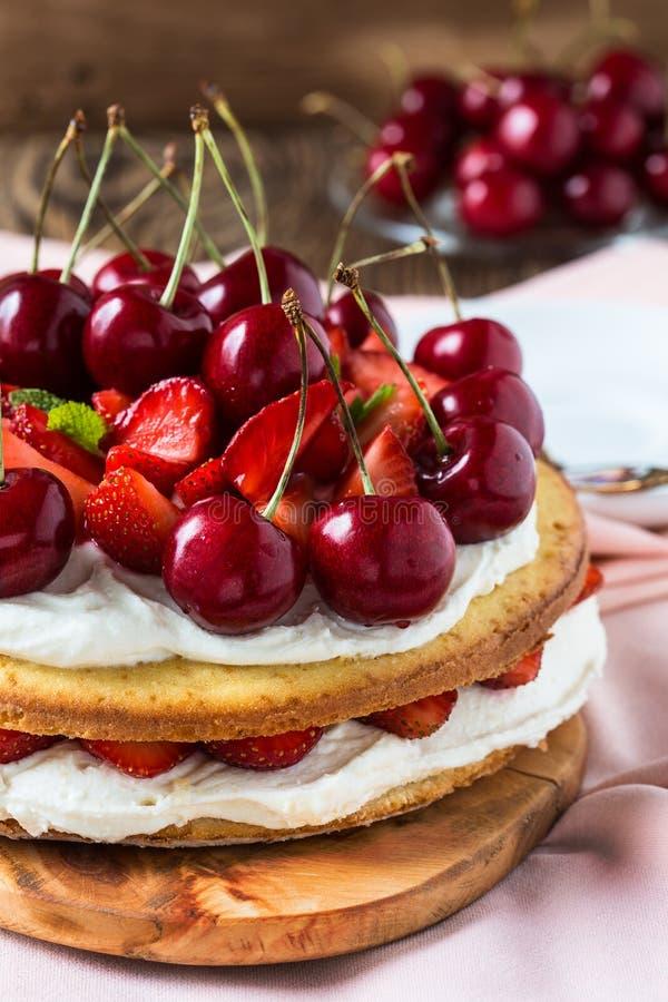 草莓和甜樱桃夹心蛋糕 免版税库存图片