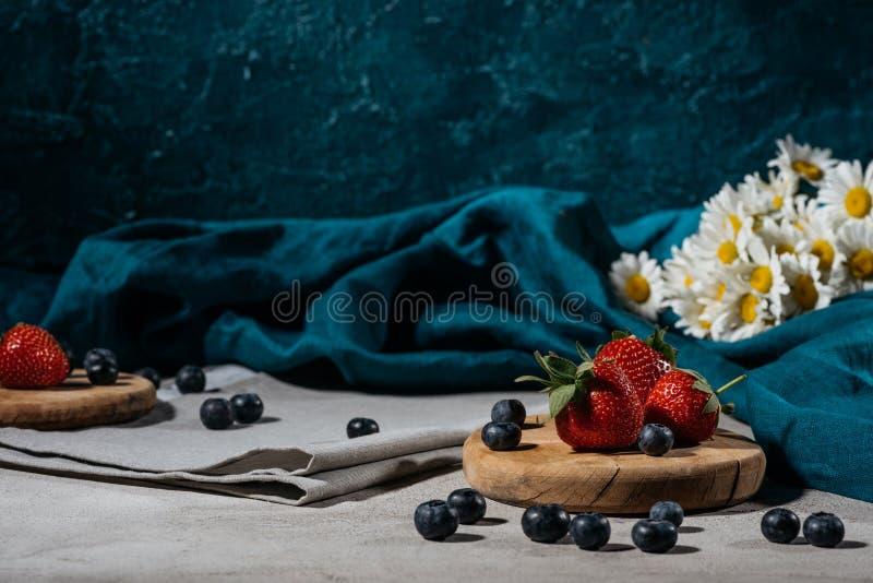 草莓和蓝莓与桌布和雏菊 免版税库存图片