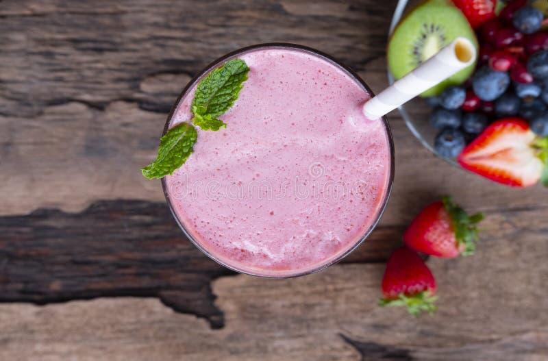 草莓圆滑的人五颜六色的果汁饮料健康在从顶视图的木背景 免版税库存图片