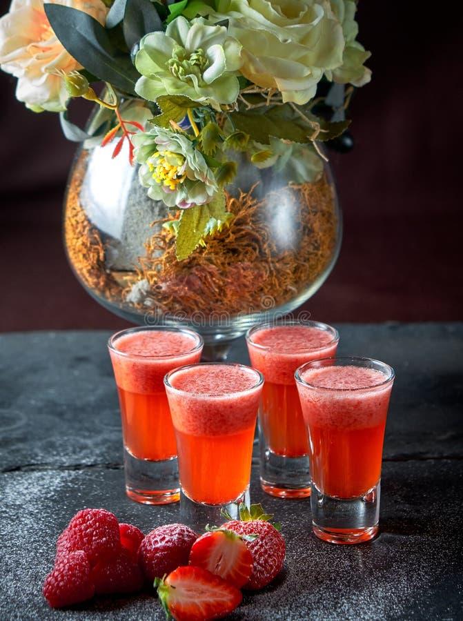 草莓在射击的酒精鸡尾酒,黑背景,酒吧 库存图片
