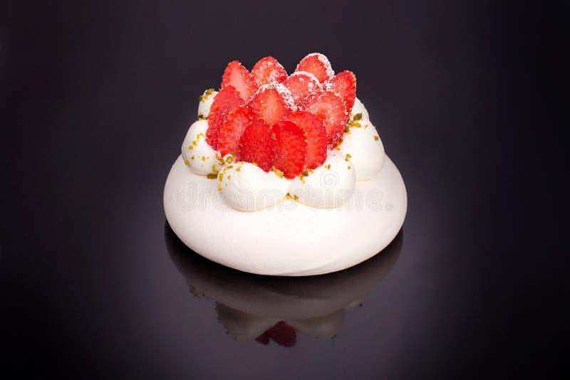 草莓在黑背景被隔绝的关闭的帕夫洛娃蛋糕顶视图 免版税库存图片