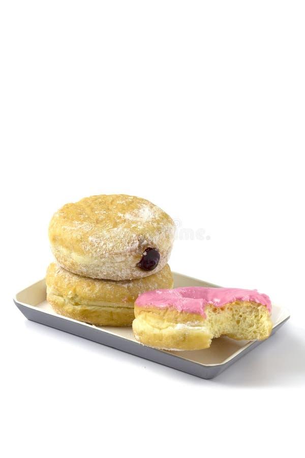 草莓多福饼被咬住投入了与夫妇油炸圈饼在被隔绝的板材在白色背景 免版税图库摄影