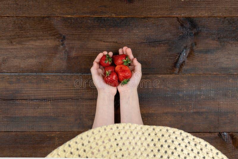 草莓对于儿童手 拿着新鲜的红色有机草莓的夏天帽子的女婴 夏天维生素背景 库存照片
